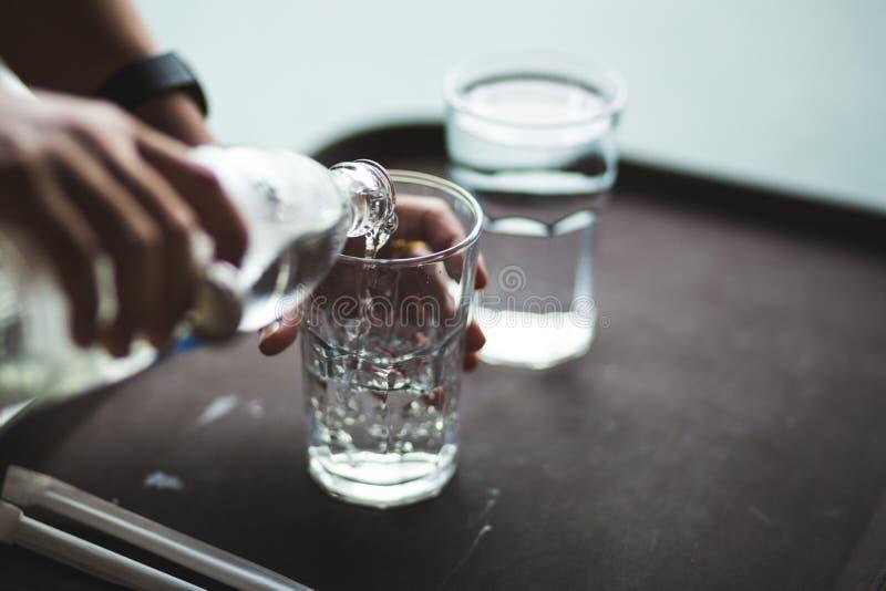 Ręki dolewania woda w szklaną butelkę obraz stock