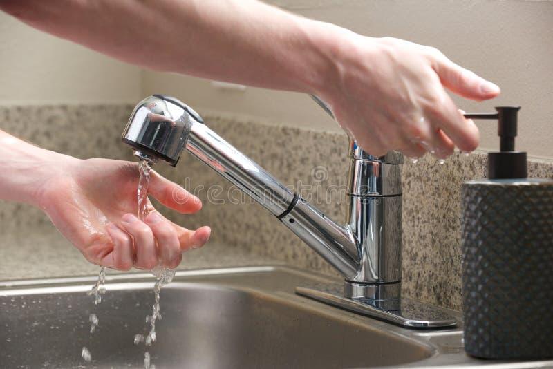 Ręki dosięgają dla mydła przy kuchennym zlew zdjęcie royalty free