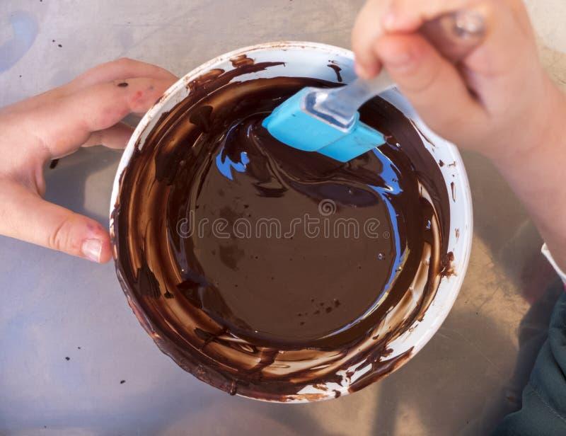 Ręki dzieci bawią się ciasto szef kuchni miesza czekoladę w pucharze zdjęcia royalty free