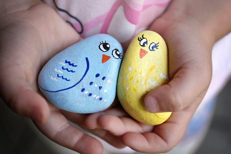 Ręki dziecka mienia przyjaźni skały troszkę Malowali jak Szczęśliwy Kolorowy Birlds fotografia royalty free