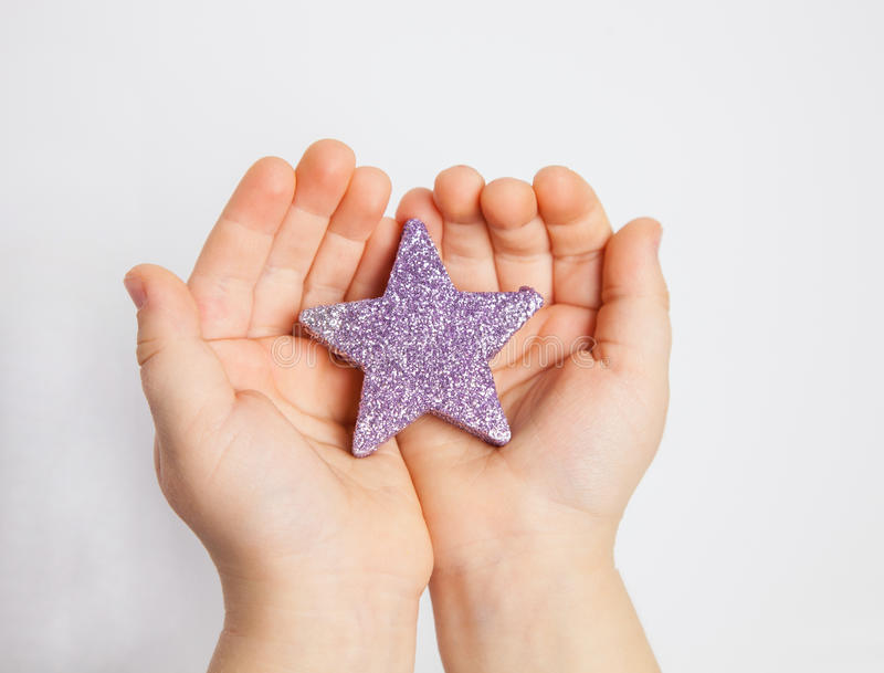 Ręki dziecko trzyma małą gwiazdę obraz royalty free