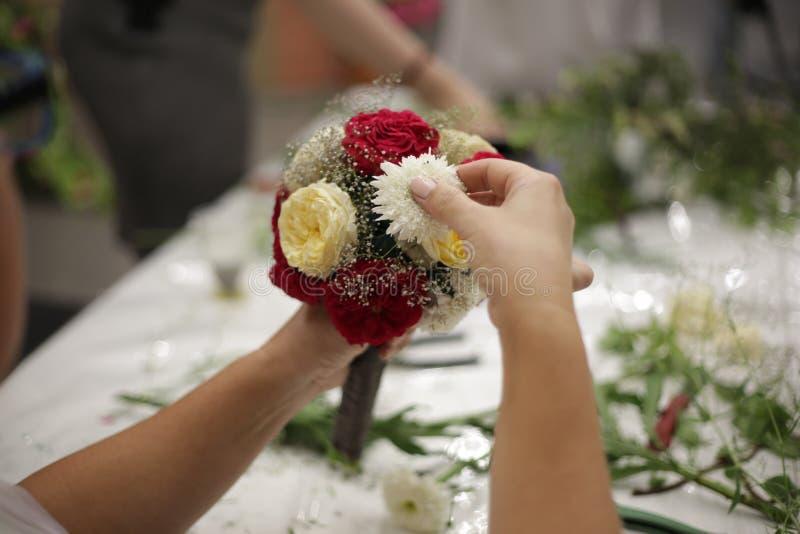 Ręki dziewczyna robią bridal bukietowi fotografia stock