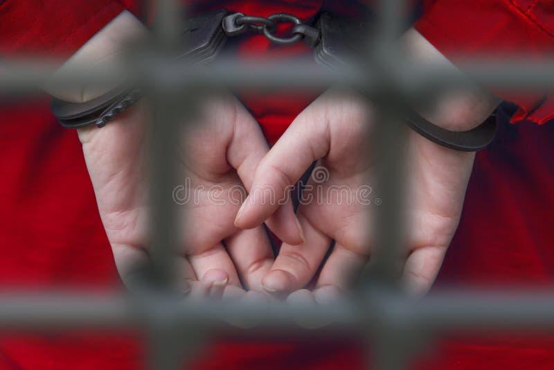 Ręki dziewczyna w kajdankach za barami więzienie fotografia royalty free