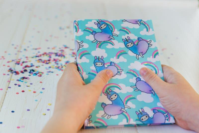 Ręki dziewczyny mienia notatnik z lamy tęczą na białym drewnianym tle z confetti i jednorożec Pomysł Girly fotografia stock