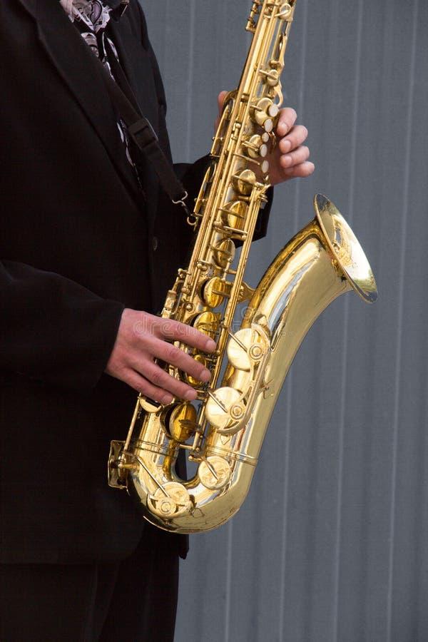 Ręki fornal bawić się na saksofonie na popielatym tle fotografia royalty free