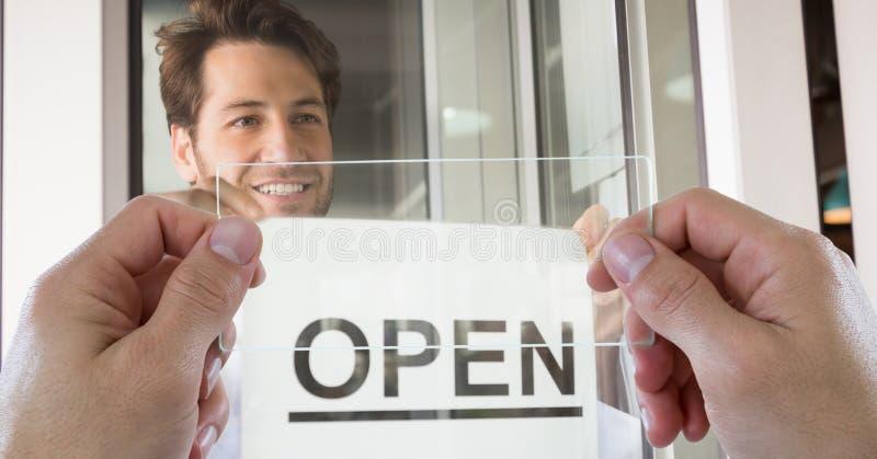 Ręki fotografuje otwartego znaka przez przejrzystego przyrządu podczas gdy mężczyzna ono uśmiecha się w sklep z kawą zdjęcia stock