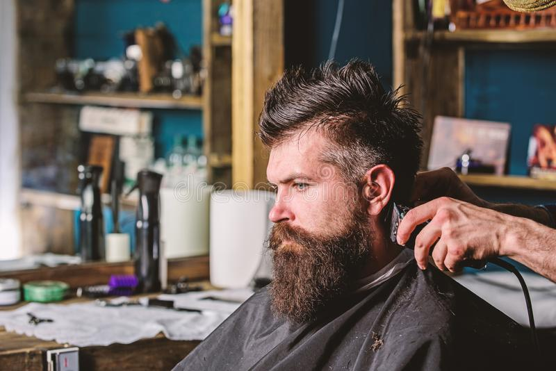 Ręki fryzjer męski z cążki i gręplą, zamykają up Modnisia brodaty klient dostaje fryzurę Zakładu fryzjerskiego pojęcie barber obrazy stock