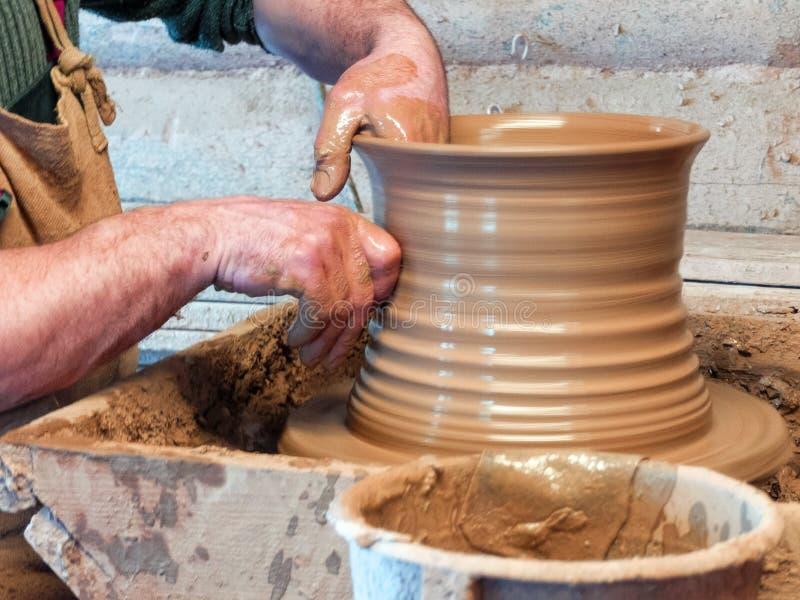 Ręki garncarka robią dużemu garnkowi fotografia stock
