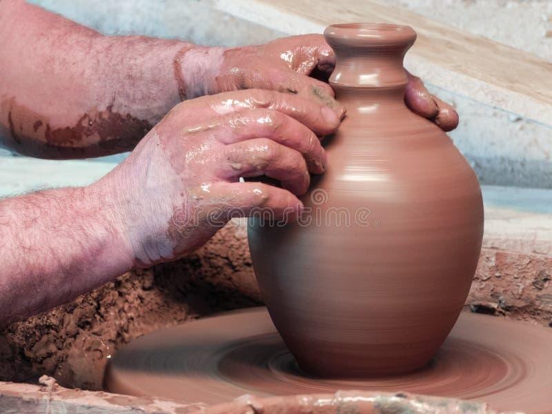 Ręki garncarka robi wazie z wąską szyją zdjęcia stock