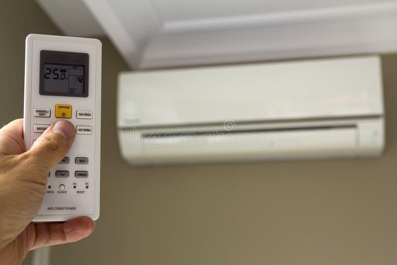 Ręki holdind kontrolna zmiana domu powietrza conditioner zdjęcie stock