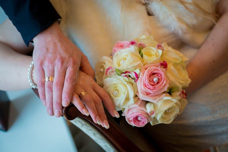 Ręki i pierścionki z pięknym ślubnym bukietem obraz stock