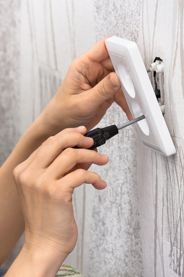 Ręki instaluje ścienną władzy nasadkę z śrubokrętem zdjęcia royalty free