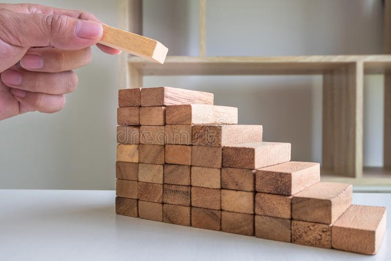 Ręki kładzenia bloki drewniani na narastającym w górę drewna wierza, ryzyka zarządzanie i strategia planu, obraz stock