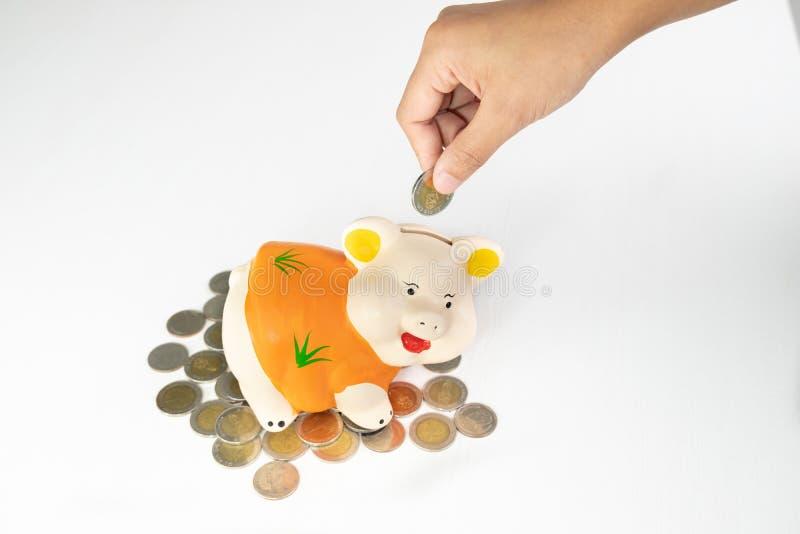 Ręki kładzenia moneta w Pomarańczowego prosiątko banka oszczędzania pieniądze z monetami wypiętrza obraz royalty free