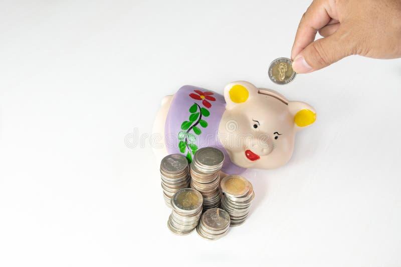 Ręki kładzenia moneta w Purpurowego prosiątko banka z monetami wypiętrza obrazy stock