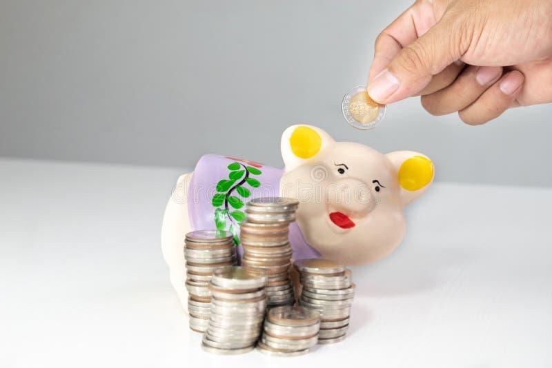 Ręki kładzenia moneta w Purpurowego prosiątko banka z monetami wypiętrza zdjęcia stock