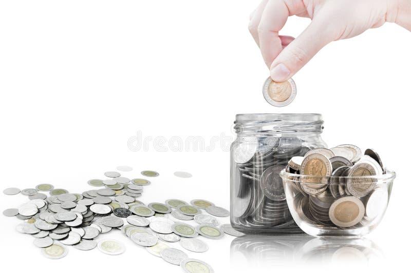 Ręki kładzenia moneta w szklanego zbiornika, monety w szklanym słoju przeciw zdjęcia royalty free