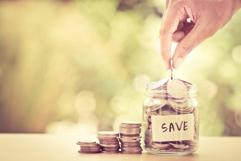 Ręki kładzenia monety w szklanym słoju dla pieniądze ratuje pieniężnego conce zdjęcie stock