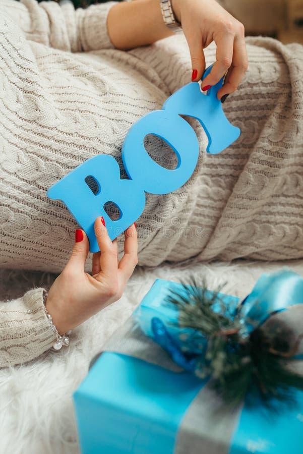 Ręki kobieta w ciąży trzymają błękitnego drewnianego szyldowego `` chłopiec ` podczas gdy kłaść za błękitną Bożenarodzeniową tera fotografia stock