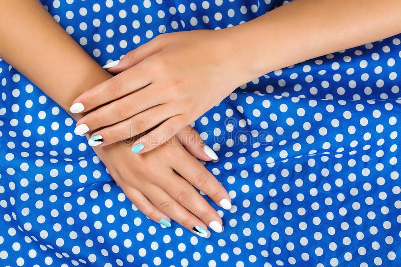 Ręki kobieta z sztuką robią manikiur na płótnie Kobiet ręki na białym błękitnym polek kropek tle Elegancki piękny manicure Przybi zdjęcia royalty free
