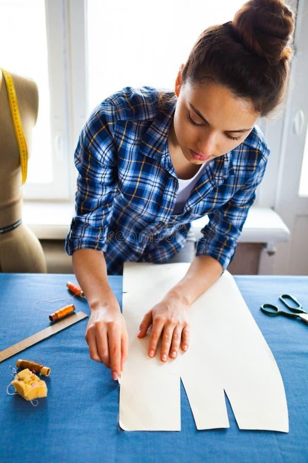 Ręki kobiety krawczyny pracujący rozcięcie rolka tkanina na którym ona obraz royalty free
