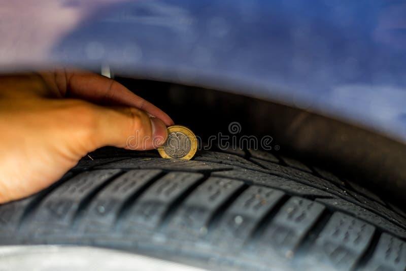 Ręki kontrola samochodowej opony profil z jeden euro monetą fotografia stock