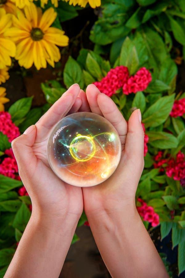 Ręki kryształowej kuli atom obrazy royalty free