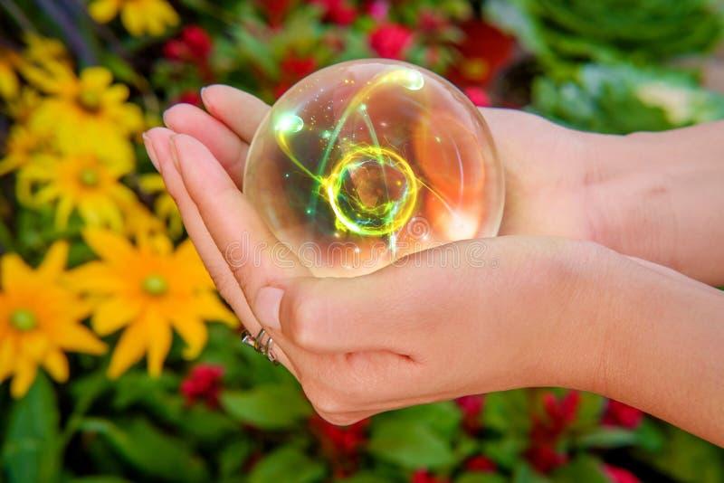 Ręki kryształowej kuli atom fotografia stock