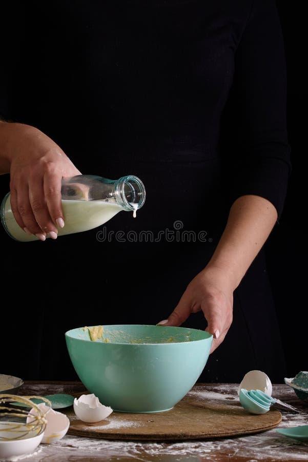 Ręki kucharz na ciemnym tle ugniatają ciasto Proces robić deserowi milka obraz royalty free