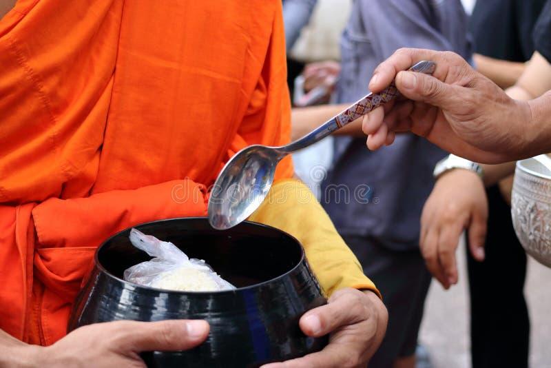 Ręki ludzie podczas gdy stawiający jedzenie Buddyjski monk& x27; s datki rzucają kulą w końcówce buddysta Pożyczający dzień zdjęcie royalty free