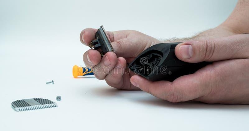 Ręki mężczyźni rozmontowywali maszynowego cążki naprawy włosy i cążków zdjęcie stock