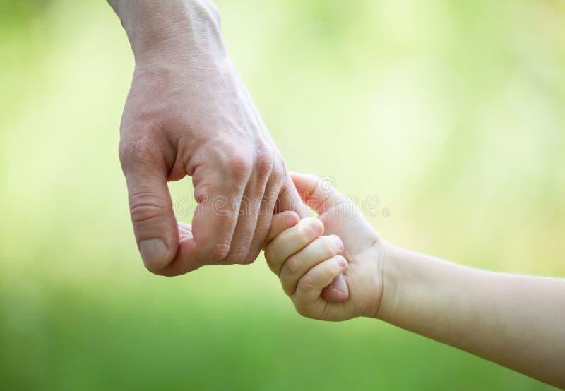 Ręki mężczyzna i dziecko trzyma wpólnie na jasnozielonym backgro fotografia royalty free