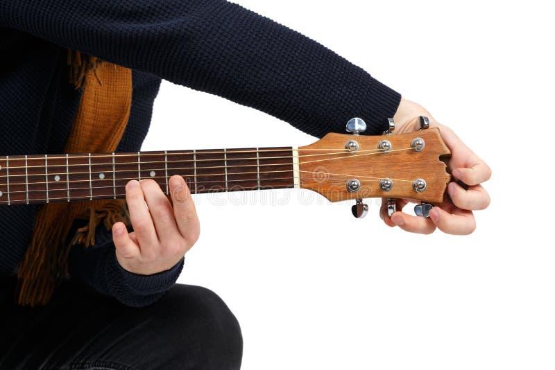 Ręki mężczyzna który nastraja dźwięka sześciostrunna gitara pojedynczy białe tło fotografia royalty free