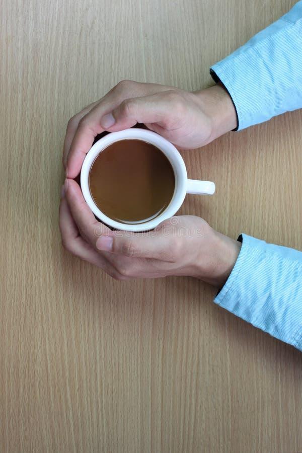 ręki mężczyzna obejmować białą filiżankę na brązu stole i fotografia stock