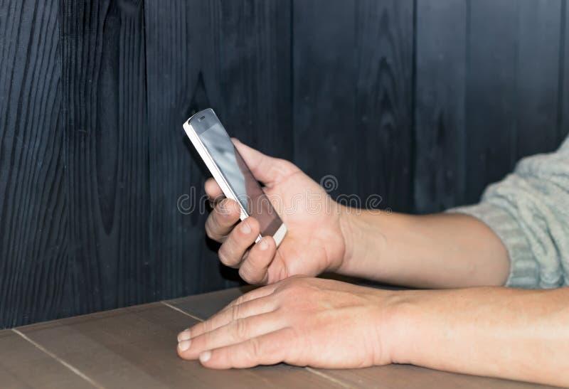 Ręki mężczyzna używa smartphone przyrząd na stole przeciw czarnej drewnianej ścianie zdjęcie royalty free