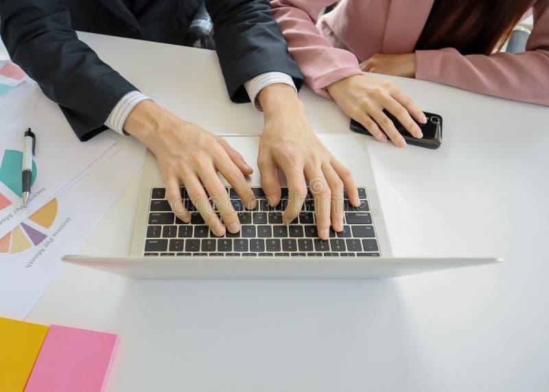 Ręki młoda biznesowego mężczyzny praca na laptopie z rękami młode biznesowe kobiety chwytają telefon komórkowego z dokumentem i p obrazy stock