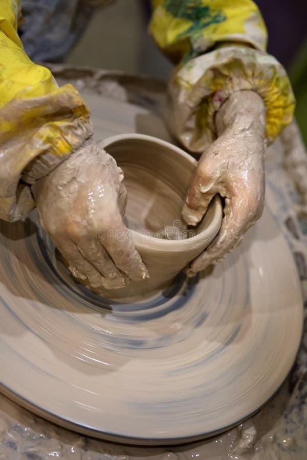 Ręki młoda dziewczyna w trakcie robić crockery na ceramicznym whe zdjęcia stock