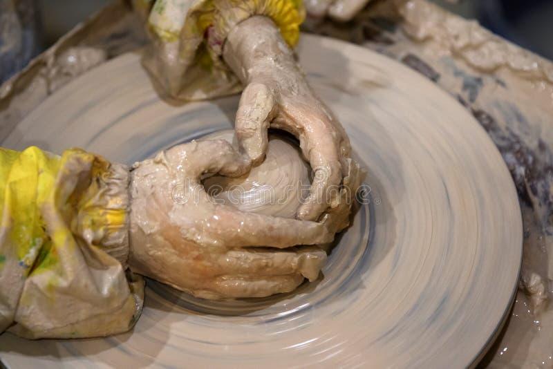 Ręki młoda dziewczyna w trakcie robić glinianemu pucharowi na ceramicznym wh obrazy stock