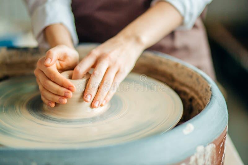 Ręki młoda garncarka, zamykają w górę ręk robić filiżanki na ceramicznym kole obraz royalty free