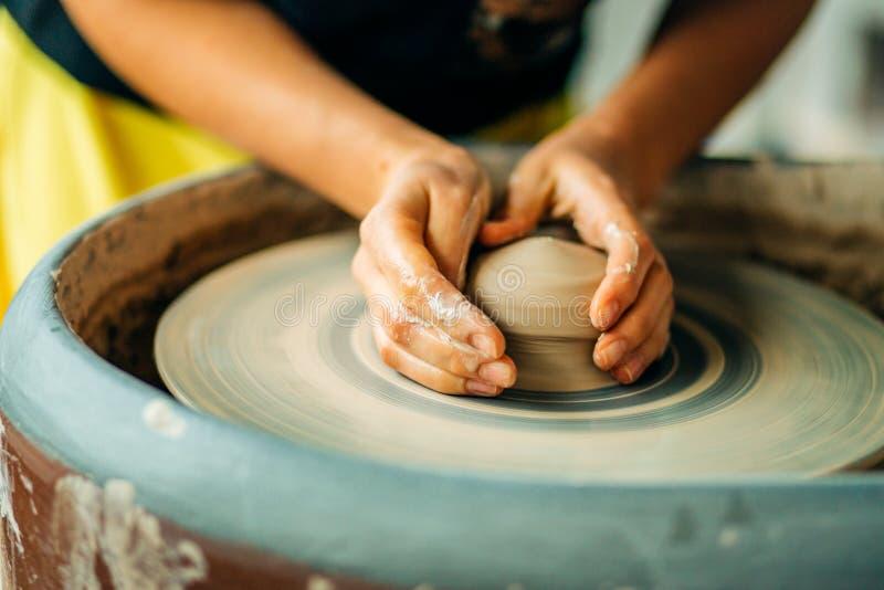 Ręki młoda garncarka, zamykają w górę ręk robić filiżanki na ceramicznym kole obraz stock