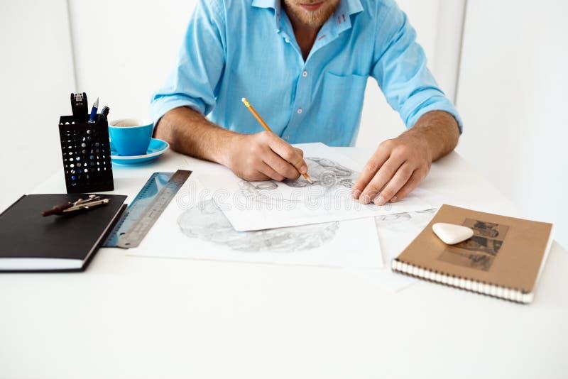 Ręki młody biznesmena obsiadanie przy stołem z ołówkowego rysunku portretem Biały nowożytny biurowy wewnętrzny tło zdjęcie royalty free