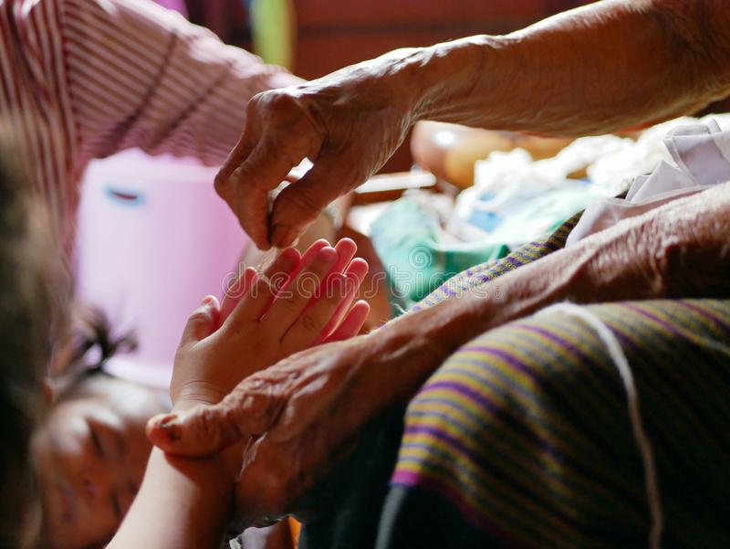 Ręki macha białego smyczkowego Sai grzech wokoło jej wnuczek ręk stara kobieta - Tajlandzki tradycyjny błogosławieństwo od stary  obrazy royalty free