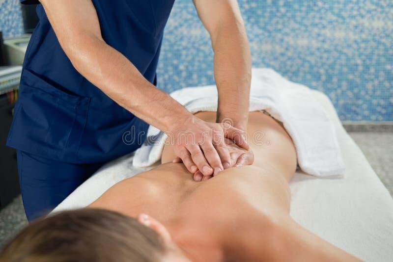Ręki masażysty rozciągania kręgosłup żeński klient w zdroju zdjęcie royalty free