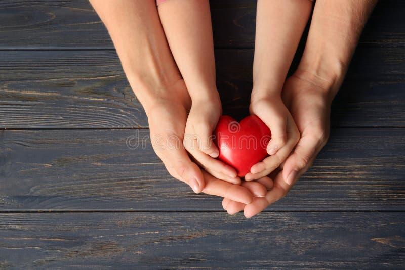 Ręki matki i dziecka mienia czerwony serce na drewnianym tle zdjęcie stock