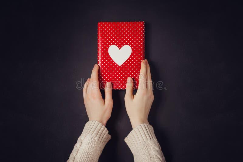 Ręki mienia czerwony prezent odizolowywający na czerni fotografia royalty free