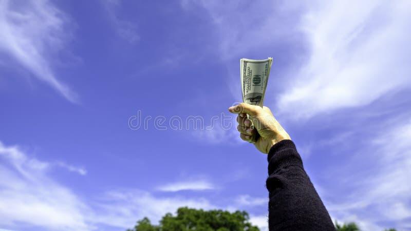 Ręki mienia dolar amerykański przeciw niebieskiemu niebu obrazy royalty free