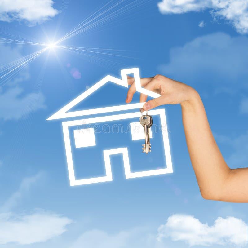 Ręki mienia domu klucz i ikona Tło niebo fotografia stock