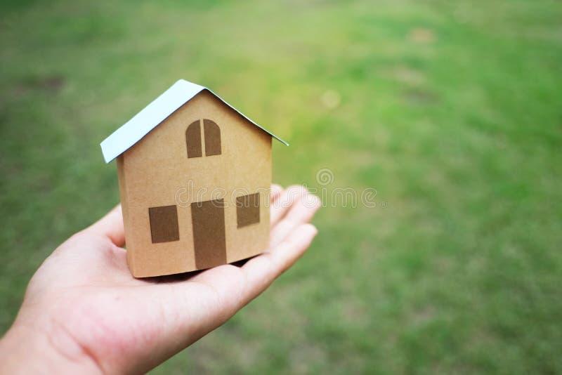 Ręki mienia domu model dla bubla, czynszu nieruchomości pojęcia z kopii trawy tłem i fotografia royalty free