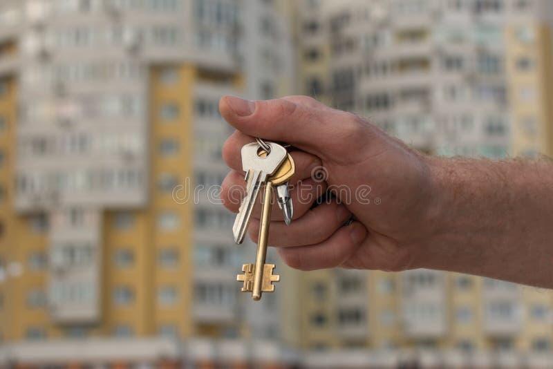 Ręki mienia klucz naprzeciw budynku tła outside obrazy royalty free