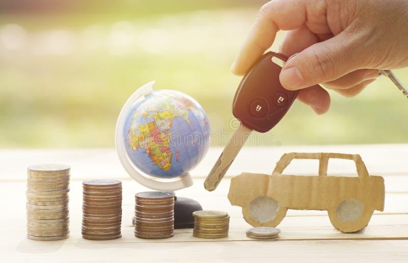 Ręki mienia klucze samochód z stosem pieniądze monety i kulą ziemską na drewno stole, plamy zieleni ogródu tło zdjęcie royalty free